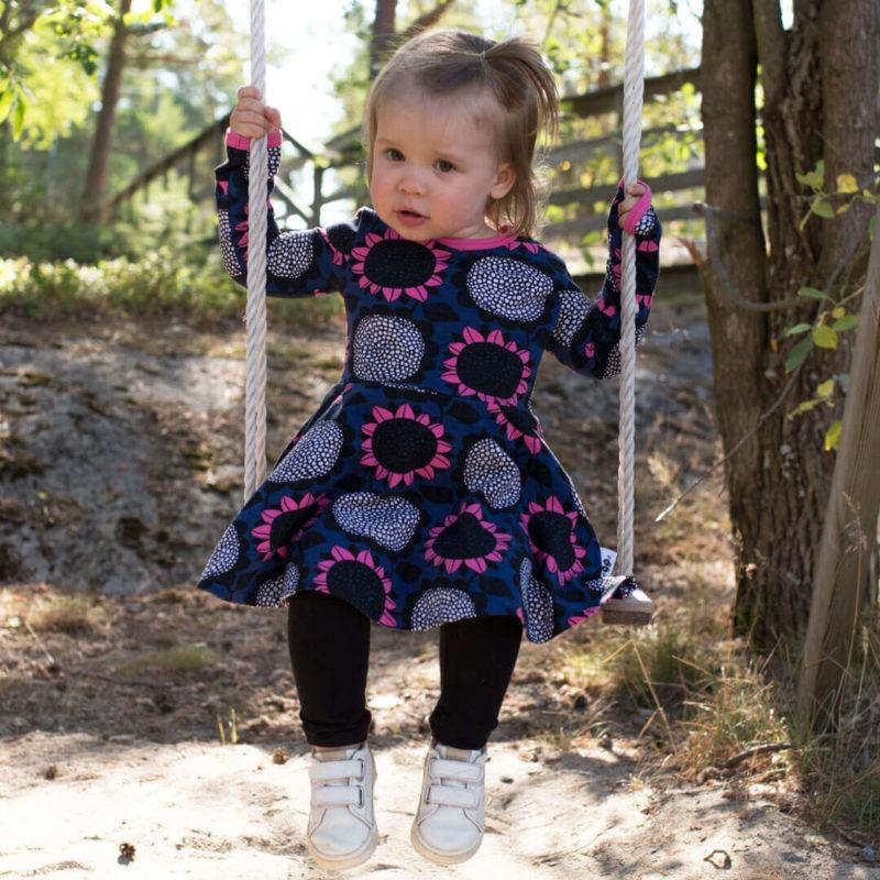 PaaPii Design Sinna lasten kellohelmamekko Auringonkukka mustikka-vaaleanpunainen keinumassa 2